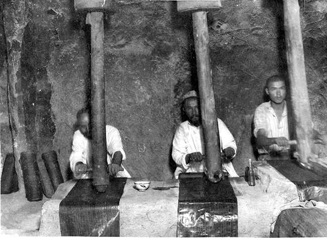 Alasha-polishers in workshop in Shımbay, Karakalpakstan. The friction caused by the constant movement of the head, in this case wooden but usually glass or stone, was an important part of the ikat-glazing process. QRSM KK 8336