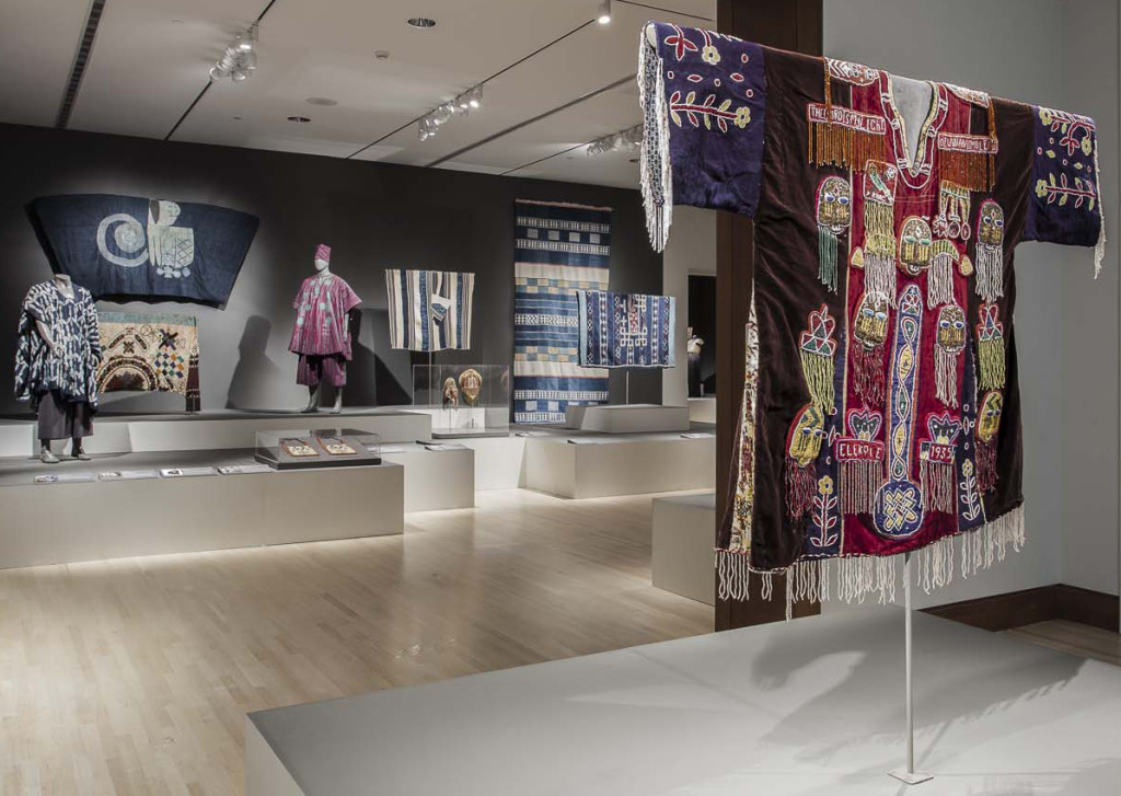 Gallery installation of 'Majestic African Textiles' at Indianapolis Museum of Art showing various West African narrow stripe woven cloths to the right, a Hausa agbaba robe on the wall left and a N'dop Cameroonian costume front left  and in the foreground a Yoruba ceremonial tunic from the early 20th century
