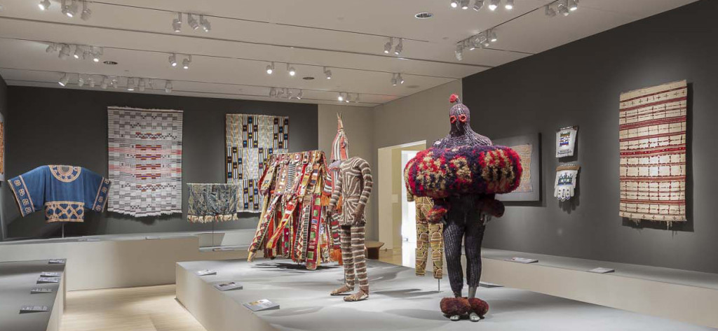 Gallery installation of 'Majestic African Textiles' at Indianapolis Museum of Art showing various narrow strip woven cloths and cultic costume