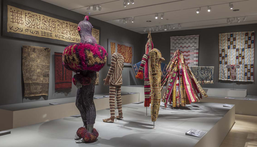 Gallery installation of 'Majestic African Textiles' at Indianapolis Museum of Art showing Central African barkcloth and raffia weaving alongside cultic costume