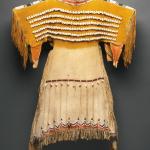 Girls dress, Cheyenne, hide, brass bells and cowrie shells, length 32 1/2  Lot 15, estimate $60,000 - 90,000