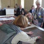 Corinne Berezuk examines the reverse of an embroidered panel, Azerbaijan, 1800 - 1840 with Edgard Hamalian, Marie Francoise Mallat, Gisela Schneider and Angela Rutherford at the Clothworkers' Centre at Blythe House in Olympia, London