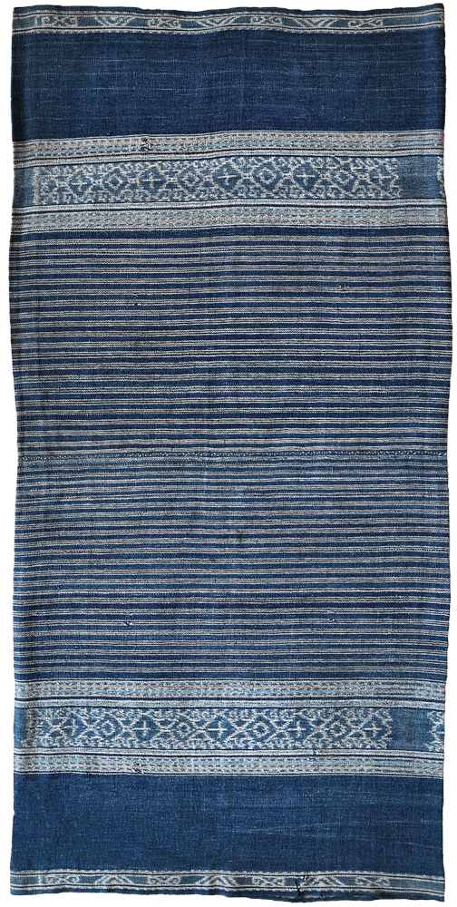 "Sarong Solor Archipelago, Alor, Bird's Head Peninsula, 1920–1950. Cotton, two panels, 0.58m x 1.19m (11'1"" x 3""11""). This piece has an unusual overall colour for its type with motifs that are reminiscent of ikan pari stingray. The collector bid on this piece at auction thinking that it was a rare Tanimbar textile. However, following his purchase, he came across a photograph that he had taken in 1981 in the Adang-speaking part of the Kabola Peninsular, Alor; it shows an elderly lady wearing a sarong with this so-far-unique design (next photo)"