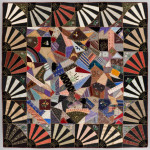 "Crazy Quilt with Fan Border; United States, initialed ""ECB"" and dated 1884 on reverse; hand pieced silk with silk embroidery; hand quilted silk backing. Neusteter Textile Collection: Gift of Guido Goldman, 2008.398."