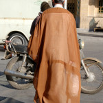 An Imam crossing the street in Kashan wears a traditional probably hand-woven robe in Yazd
