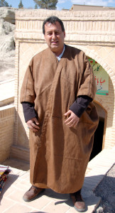 Tour Leader Vedat Karadag tries on a camelhair robe, some of the last to be woven