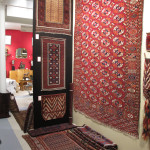 A Central Asian corner on Brian MacDonald's stand including a Baluch rug and sofreh and a Tekke Turkmen main carpet and Yomut okbash.