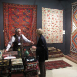 Chris Legge talks with a client in front of an Ersari Turkmen carpet and dazzling Qashqa'i kilim