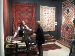 Chris Legge talks with a client in front of an Ersari Turkmen carpet and dazzling Qashqa'i kilim