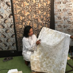 Batik artist using wax resist on cotton batik - part of the display of exhibition of Indonesian textiles from The Jakarta Textile Museum organised at The fair by Curtis and Margaret Keith Clemson