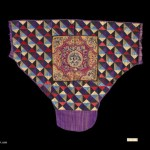 "Baby Carrier, China Zhuang, 20th Century. 3' x 2' 6 3/4"" (91.4 x 78.1cm); Cotton, silk; quilting and appliqué, embroidery in silk on ceter panel. Baby carrier with a field of multi-colored tabby woven cotton fabrics, cut into triangles and quilted. Center panel formed of appliquéd satin elements in scalloped pattern, and then embroidered in silk. Cloth ties are cut off. Roger Hollander Collection - Primary collection"