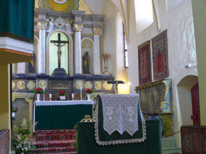 The altar of a functioning church with rugs on the wall