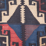 Slit-tapestry was most commonly used to weave kilims in Tusheti. The comb tooth effect on the vertical lines, stepped diagonal lines and hooked curls are decorative solutions to the limitations of this technique. The diamond motifs between the main güls provide a meeting point where there is a change between the positive and negative elements of the pattern being woven in white.