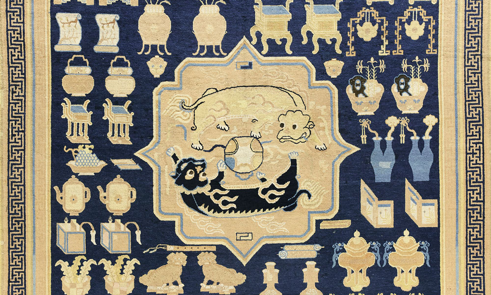 "Lot 71, The Larsson lion-dog medallion with 'hundred antiques' dais carpet, China, first half 18th century. 2.55 x 2.73 m (8' 4"" x 8' 11""). Sotheby's, London, 6 November 2018, estimate £50-80,000"