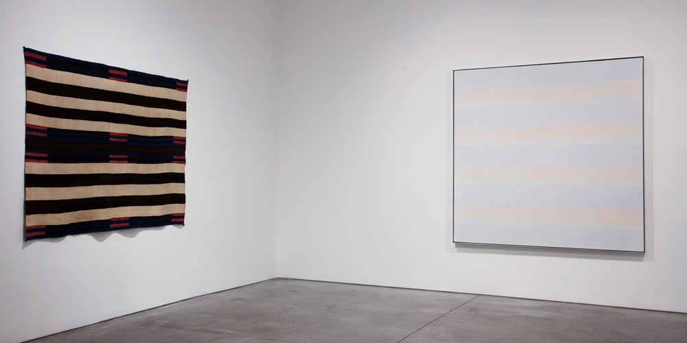Installation view of a Classic Second Phase Chief's Blanket with Manchester Bayeta (left), Navajo, circa 1840, and Untitled #2 (right), Agnes Martin, 1992, Acrylic and graphite on linen. 'Agnes Martin / Navajo Blankets', Pace Gallery, New York