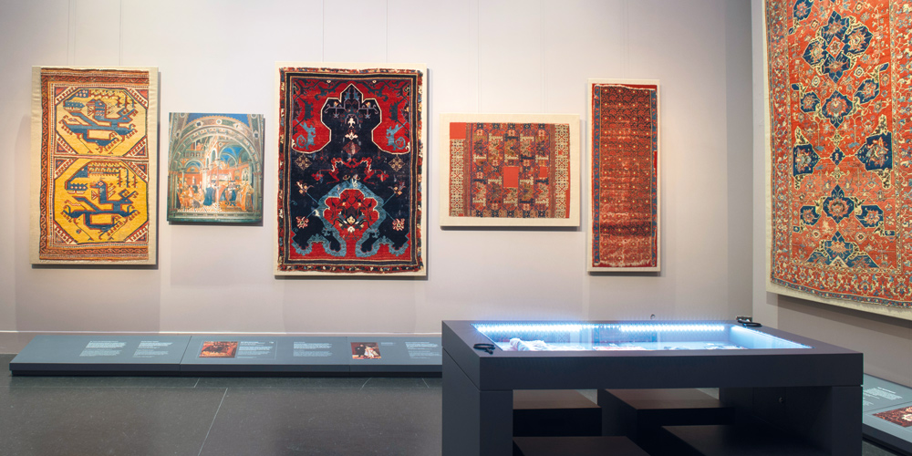 View of the new permanent carpet installation 'Dream and Trauma' at the Museum of Islamic Art in Berlin, showing iconic highlights from the museum's collection such as the Bode cloudband prayer rug and the early Anatolian dragon and phoenix carpet