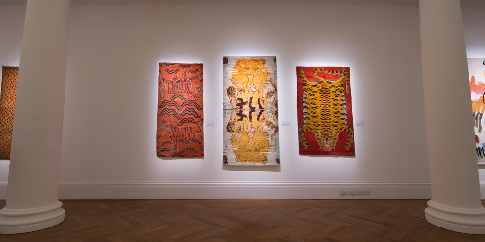 'Orange Double Tigers' (left) and 'Red Flayed Tiger' (right), paired with rug designed by Rose Wylie, hand-knotted in hand-spun wool by Christopher Farr for Tomorrow's Tigers (centre), on show at Sotheby's, London, 29 January – 4 February 2019.