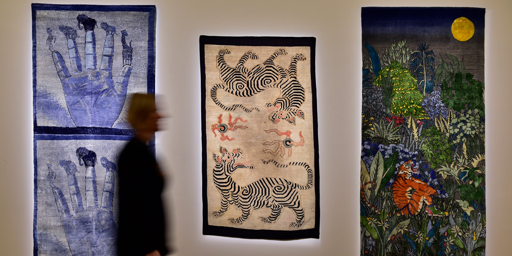 'Double Zebra Tiger', c.1900–50, wool and cotton, 1.60 X 0.92m, on loan from David Sorgato Collection, paired with 'Map of What is Effortless', Francesco Clemente, 2018–19, hand-knotted, hand-spun, hand-dyed natural silk, 2.25 X 1.04m, courtesy of the Blain Southern Gallery (left), and rug designed by Raqib Shaw for Tomorrow's Tigers (right), on at Sotheby's, London, 29 January – 4 February 2019.