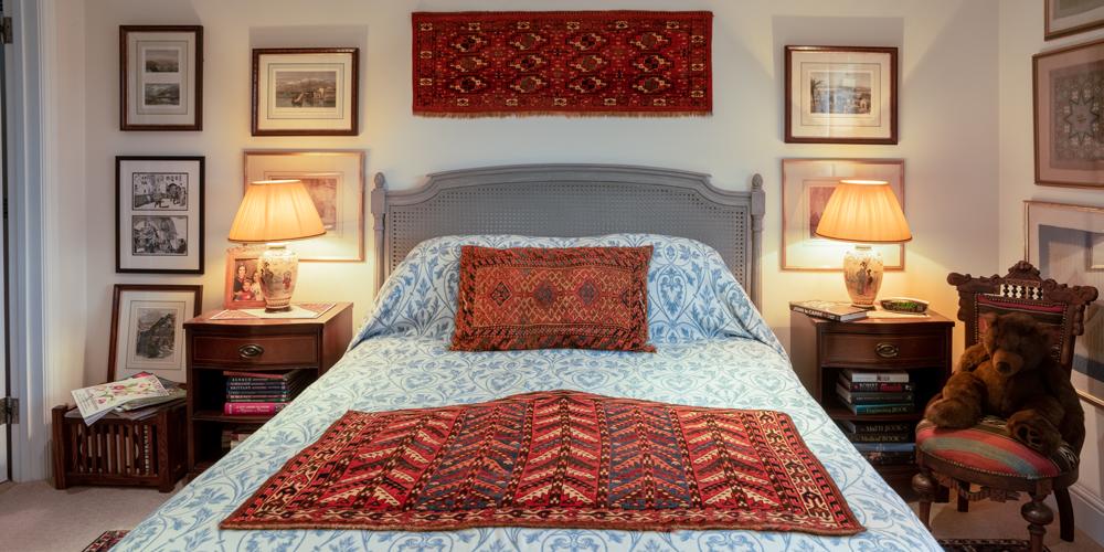 """Bell household guest bedroom: on the wall, Yomut Turkmen 12-gül torba, Turkmenistan, 19th century, 0.43 x 1.22 m (1' 5"""" x 4' 0""""); on the bed, Yomut Turkmen pentagonal 'tree' asmalyk, Turkmenistan, 19th century, 0.79 x 1.13 m (2' 8"""" x 3' 8"""")"""