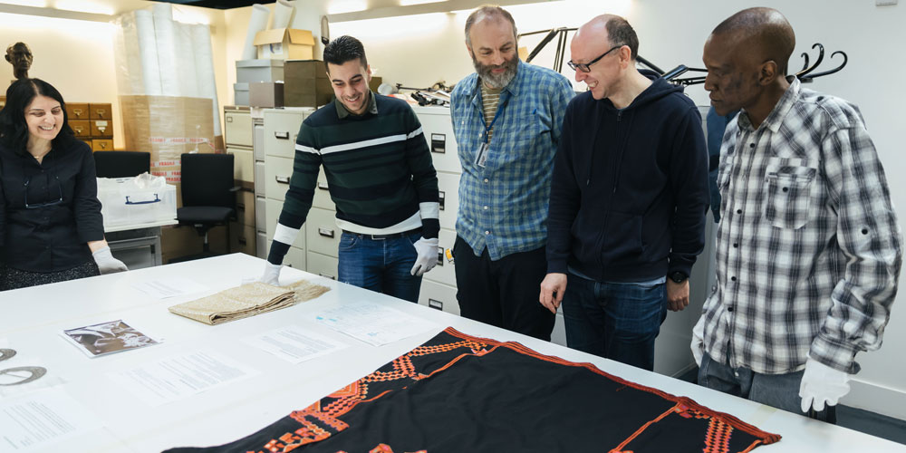 Museum staff work with volunteers on mounting the textiles for the final display. Photograph by Ian Wallman.