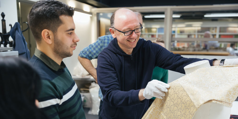 Volunteer Hussein and curator Andrew work on mounting a silk scarf from Damascus. Photograph by Ian Wallman.