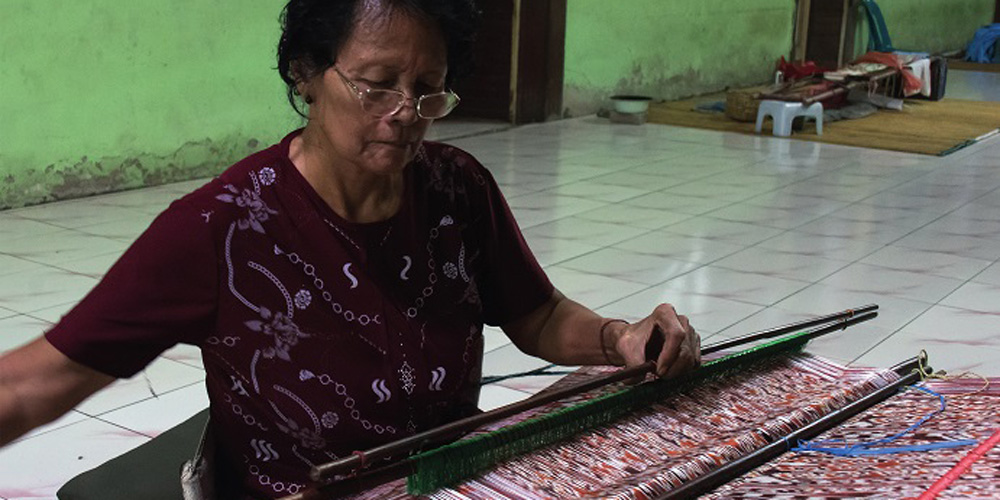 Iban weaver working on a externally-braced backstrap loom to weave ikat cloth (Malaysia, Sarawak, Rumah Gare, 2016) © Rémy Prin.